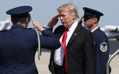 El presidente Donald Trump hace un saludo militar luego de bajar del avi...