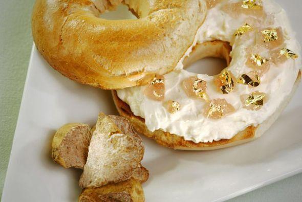 Este bagel con queso crema con aceite de trufa blanca, hojas de oro, una...