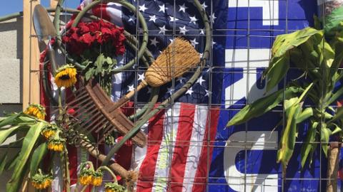 Elementos agrícolas, una bandera y un cartel de Trump en muro anti-Trump