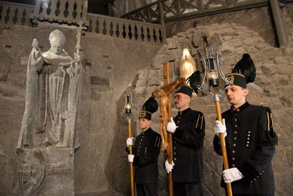 Mineros polacos con uniformes ceremoniales junto a la estatua de sal del...