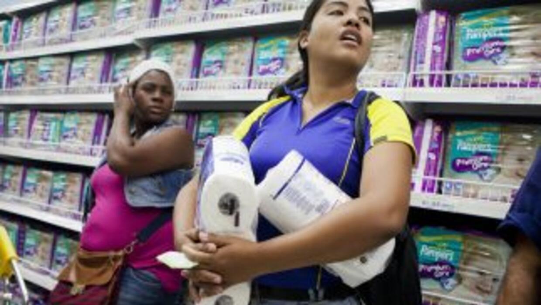 Una mujer recibe cantidad racionada de papel hiegiénico en un automercad...