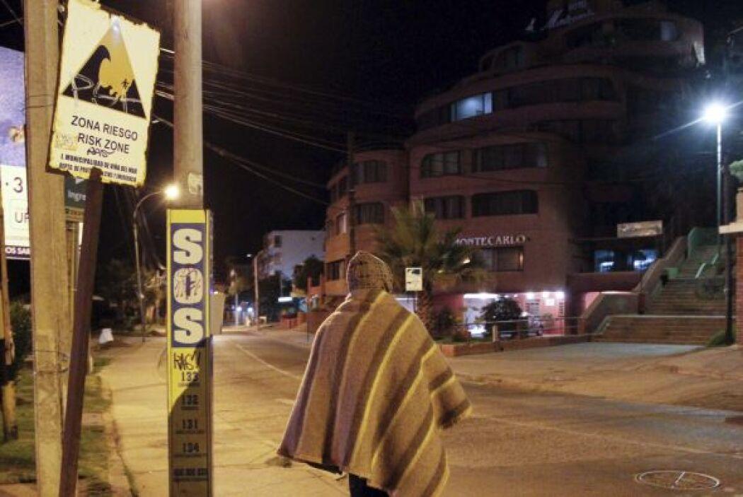 Un hombre camina junto a una señal de alerta de tsunami durante la madru...