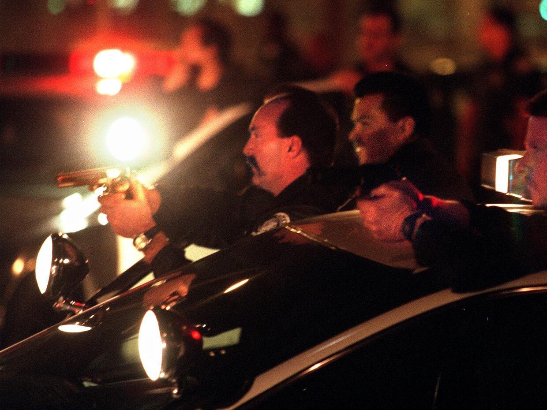 Agentes de la policía de Long Beach en California apuntan sus arm...