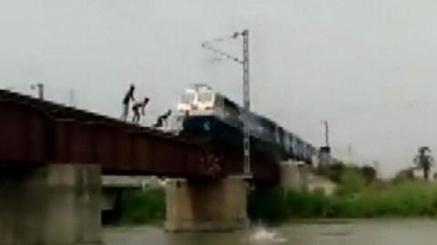 Jóvenes saltan de las vías de un tren en la India