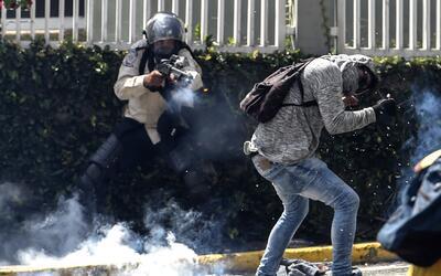 Un policía nacional dispara a quemarropa contra un manifestante en Caracas.