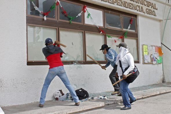 Otros portaban palos y comenzaron a romper los vidrios de las ventanas.