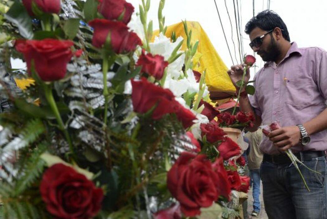 Las tradicionales flores rojas abundan pro las calles de Nueva Delhi, es...