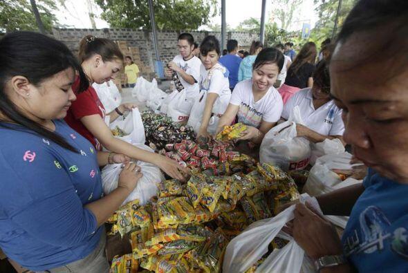 Voluntarios filipinos se preparan para repartir bolsas con suministros p...