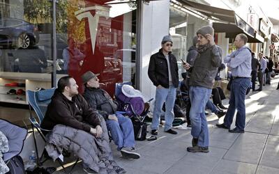 Nick Tobin, izquierda, espera en línea para ser el primero pagar el depó...