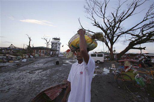 Un filipino carga algunos de los bienes que pudo salvar entre los escomb...