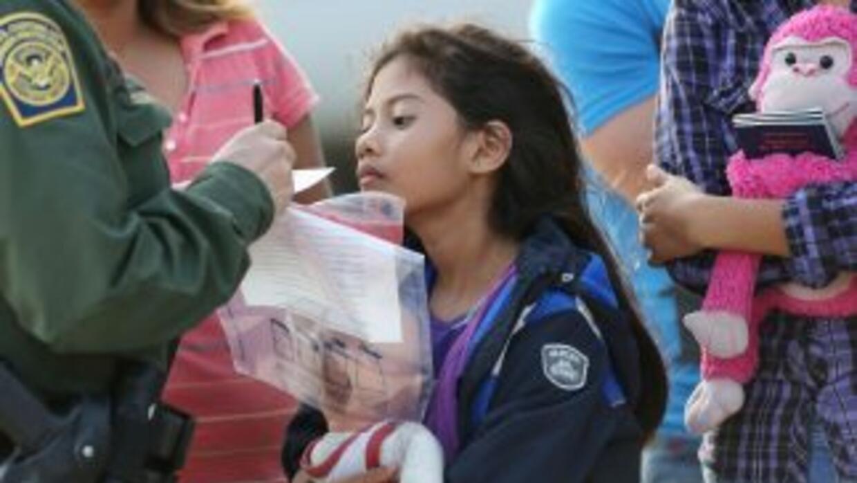 Un agente de la Patrulla Fronteriza toma los datos de una niña indocumen...