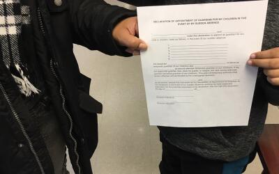 María (nombre ficticio) y su hijo sostienen una carta de custodia...