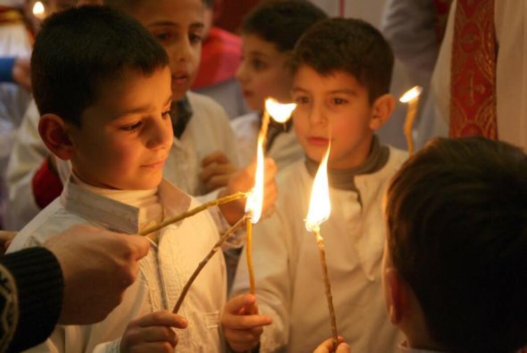 Los niños encendieron velas durante la ceremonia religiosa en Irak.
