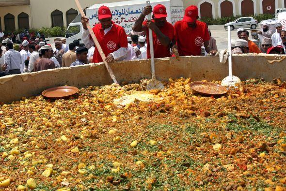 Hombres de Omán revuelven los ingredientes para preparar uno de su plati...
