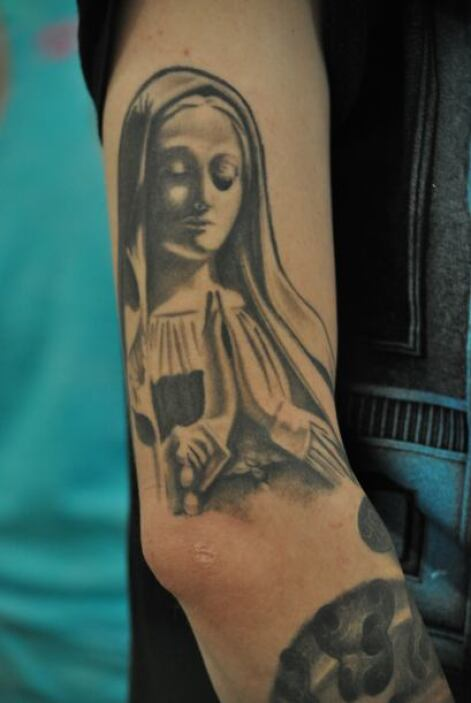 La Virgen tatuada en los brazos...