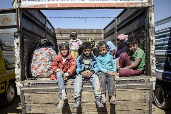Niños kurdos se sientan en un camión después de cruzar la frontera sirio...