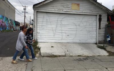 Dos mujeres caminan frente a la cochera de una casa en Hollywood, Califo...