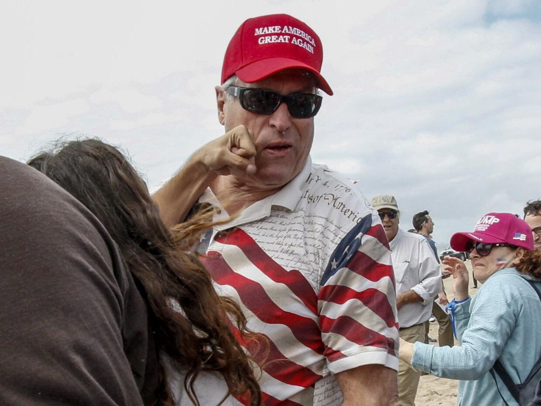Un hombre con una camiseta de 'Make America Great Again' recibe un pu&nt...
