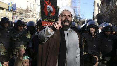 Rodeado por policías, un clérigo musulmán habla a la multitud durante un...