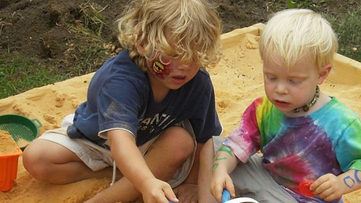 Kids communicating and working together in sandbox.