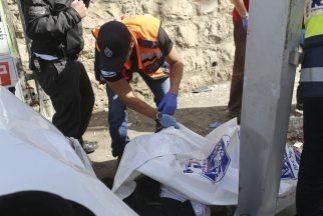 Un policía compreba el cuerpo de un fallecido en el lugar donde se produ...