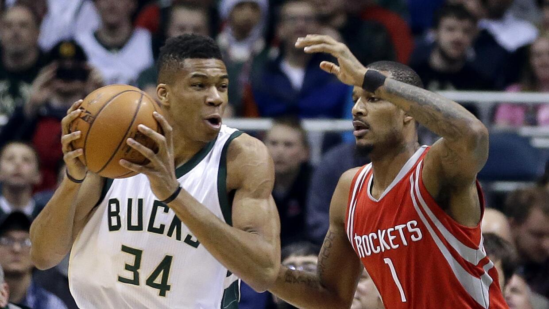 Giannis Antetokounmpo, de los Bucks de Milwaukee, trata de eludir a Trev...