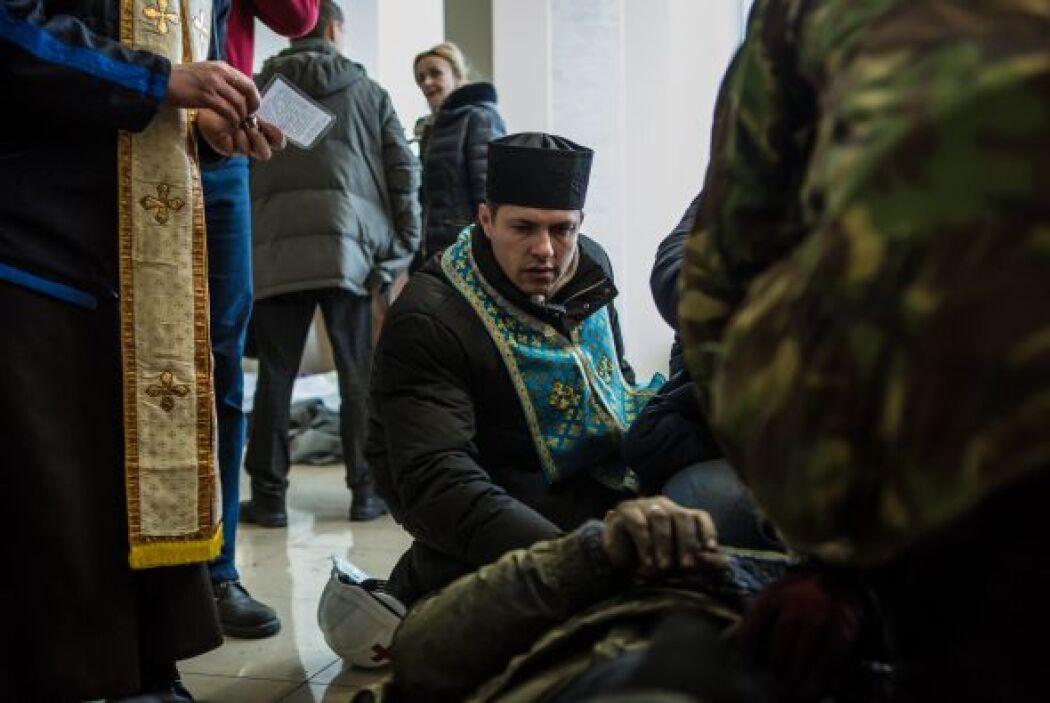 Un sacerdote asiste a uno de los manifestantes caídos en las protestas d...