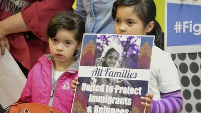 Dos niños con un cartel en mano piden al gobierno de Donald Trump que pr...