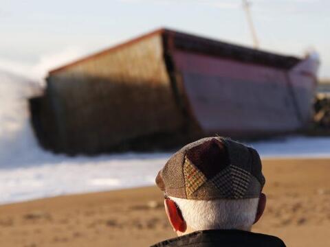 """Un hombre observa el carguero vizcaíno """"Luno"""", que ha q..."""
