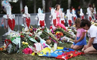 People visit a makeshift memorial setup in front of Marjory Stoneman Dou...