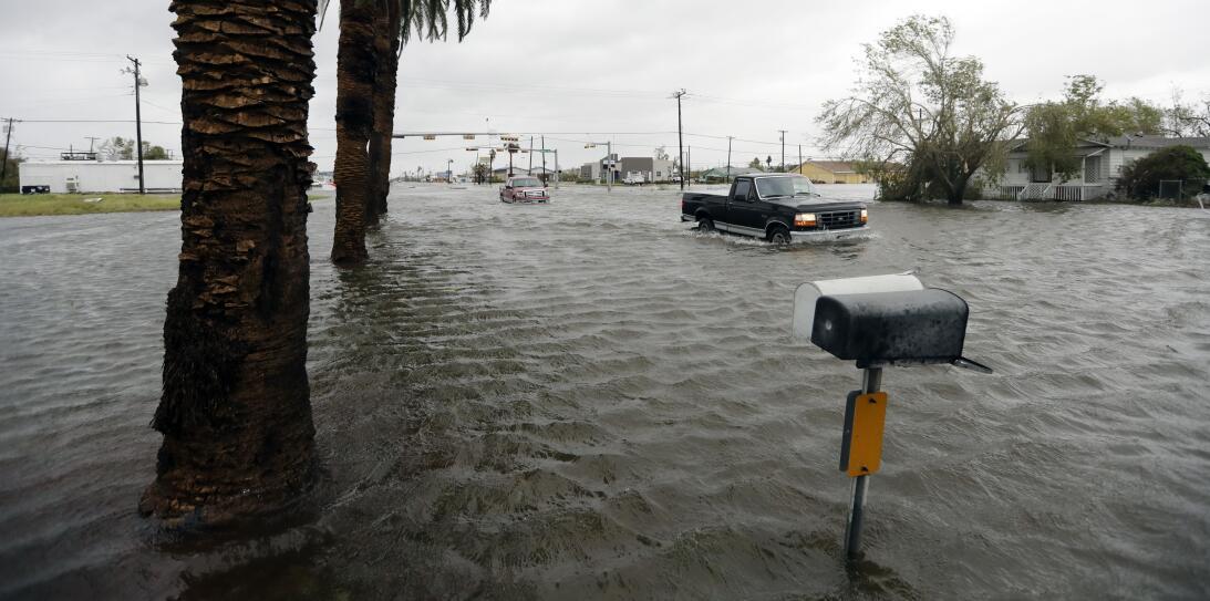 Varios vehículos avanzan en medio de una inundación provocada por el hur...