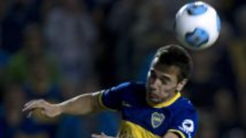 El delantero Lagos (abajo) pelea un balón con un jugador de Boca Juniors...