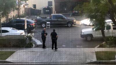Dos policías vigilan un área donde se reportó un tiroteo en Long Beach,...