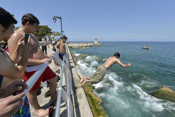 Un joven salta en el mar Mediterráneo , mientras que otros lo ven en la...