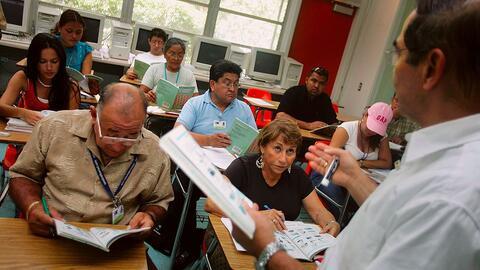 Un docente enseña inglés a un grupo de adultos inmigrantes...