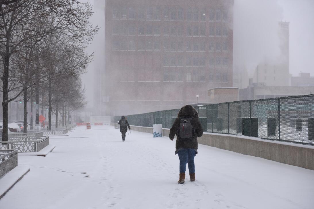 Gente caminando por una larga avenida de Detroit completamente cubierta...