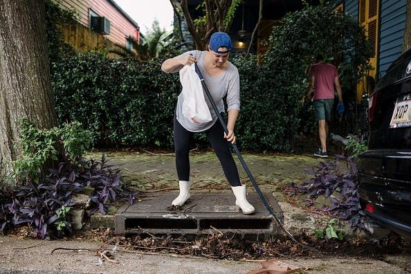 Una mujer limpia el alcantarillado frente a su casa para que el agua pue...