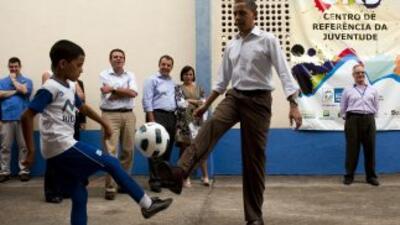 El presidente Obama juega al fútbol con un niño durante su visita a la f...