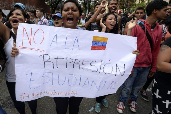 Una mujer posta un cartel pidiéndole al gobierno que cese la represión.