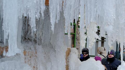 Turistas le toman una fotografía a una fuente congelada en el Bry...