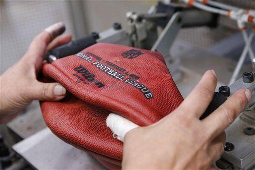 Una máquina de costura le va dando la forma ovoidal al balón de fútbol a...