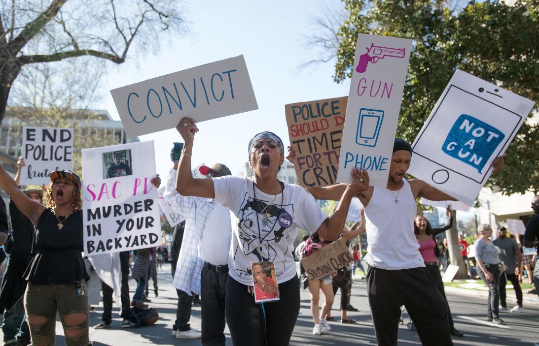 Manifestantes de 'Black Live Matters' marchan con carteles donde...