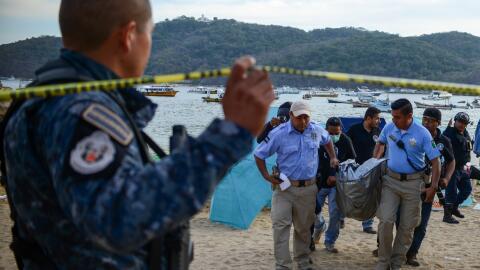 Personal forense traslada un cuerpo en el puerto de AcapulcoPersonal for...