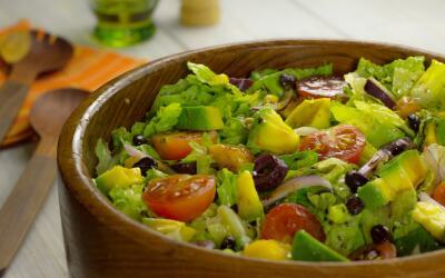 Ensalada verde con vegetales, granos, fruta y vinagreta balsámica.