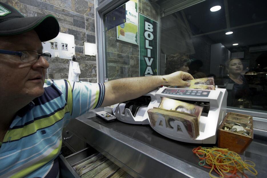 Un hombre cuenta dinero venezolano en una casa de cambio ubicada en la p...