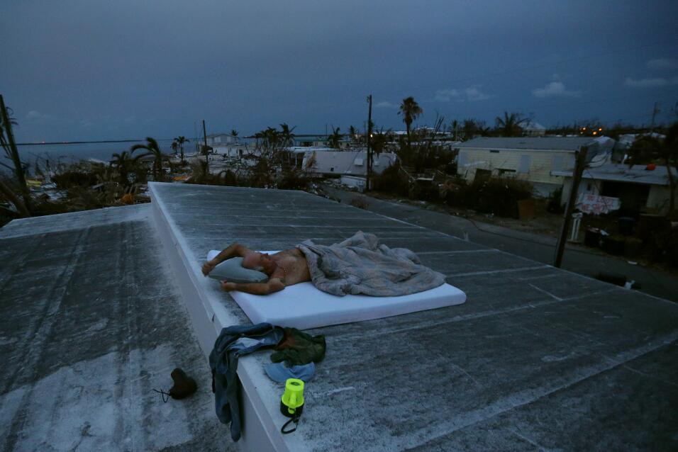 Matt Finn seeks a breeze as he lays down on the roof of his house that i...
