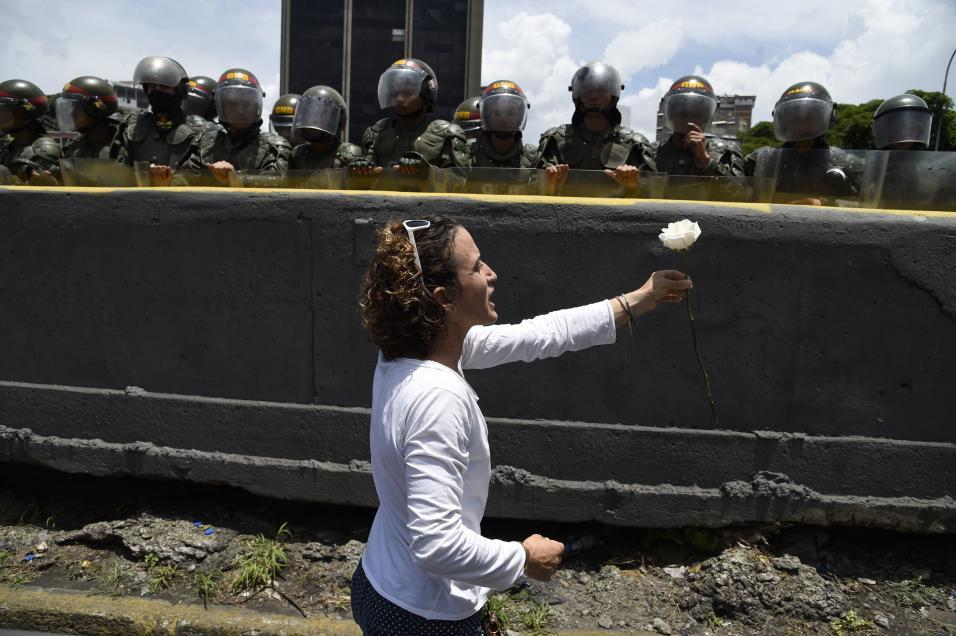 A woman dressed in white offers a flower to riot troops during a woman&#...