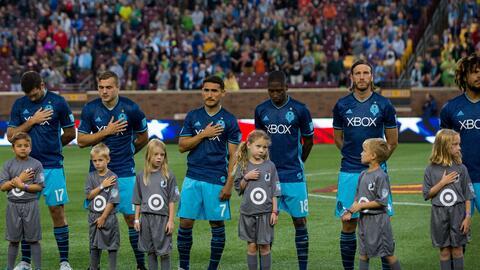 Jugadores de Seattle Sounders observan el himno nacional de EEUU.
