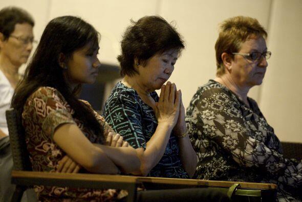 Gente reza por las víctimas del Malaysia Airlines en una iglesia cerca d...