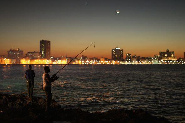 Un grupo de hombres se reúne al atardecer para pescar a lo largo...
